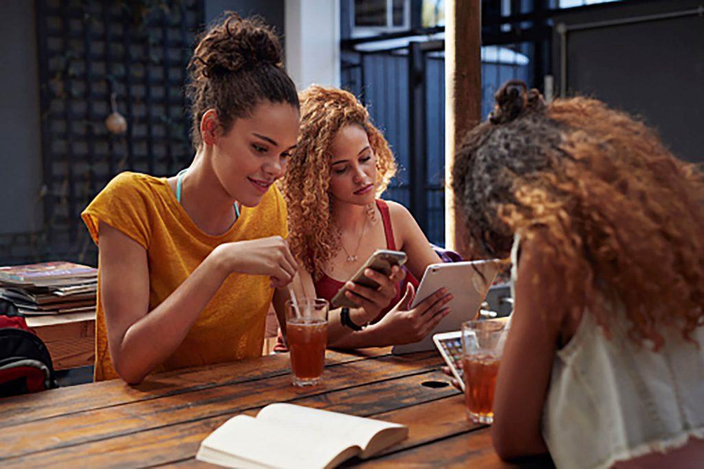 Girls at table looking at phones